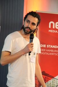 Tarek Müller hat an diesem Abend nicht nur die Rolle des Jurors inne, sondern führt das Publikum im betahaus durch den spannenden Abend.
