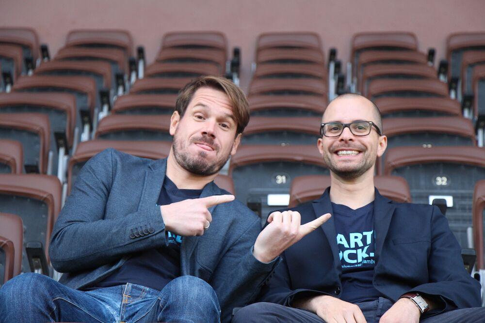 Christoph Ihl und Sebastian Tempel vom Startup Dock der TU Harburg haben Spaß auf der Tribüne des Millerntor-Stadions