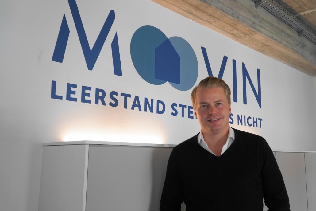 Geschäftsführer Fabian Mellin vor dem moovin-Logo im Büro in der Hamburger Sternstraße.