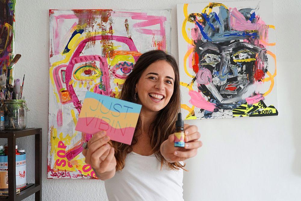 Gründerin Sabela Garcia Cuesta vor zwei ihrer Bilder und mit dem Motto und dem Fläschchen von Art District.