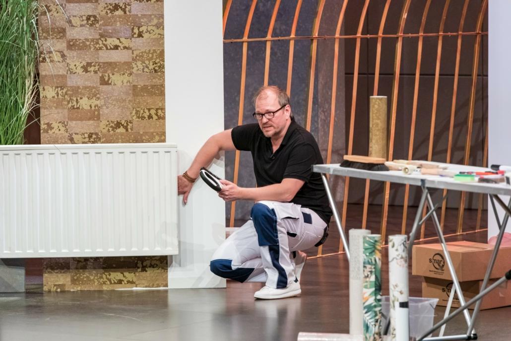 Michael Heide zeigt, wie seine Tapezierbürste SmartQ auch hinter Heizkörper kommt. (Foto: TVNOW / Bernd-Michael Maurer)