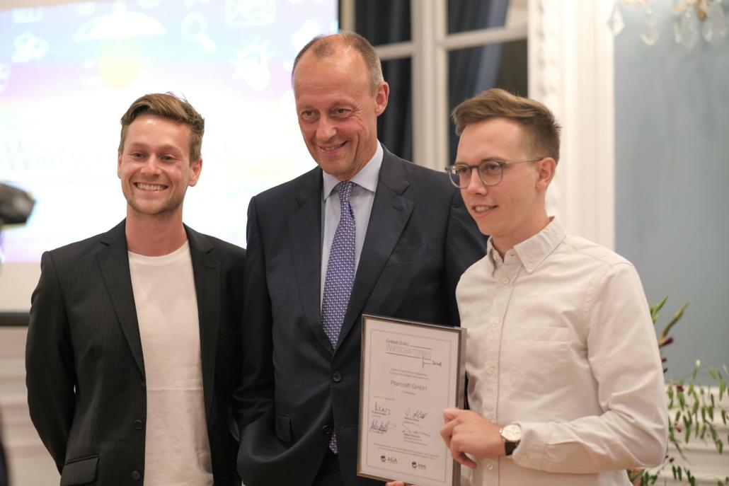 Friedrich Merz mit den Gewinnern Julian Wiedenhaus (l.) und Till Zimmermann (r.) von Plancraft.